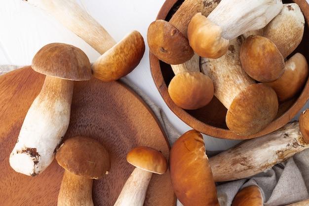 Funghi porcini marroni sullo sfondo di un vassoio di legno. vista dall'alto.