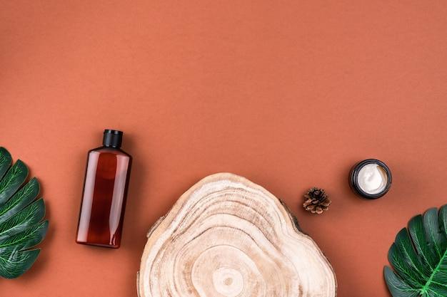 Bottiglia marrone di lozione, crema, shampoo su sezione trasversale in legno
