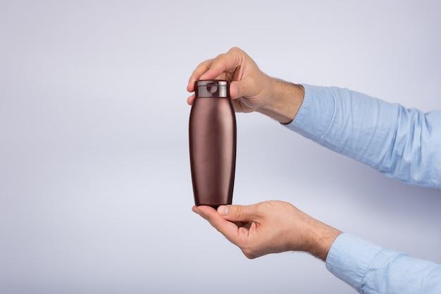 Bottiglia marrone di shampoo o lozione in mano maschio su bianco