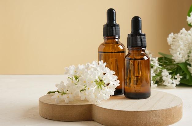Flacone marrone con contagocce per oli o sieri cosmetici e un ramo di lilla bianco su fondo beige, cosmetici naturali per la cura della pelle del corpo e del viso.