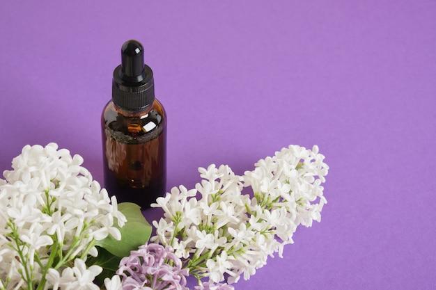 Flacone marrone con contagocce per oli o sieri cosmetici e lilla bianco su sfondo viola brillante, cosmetici naturali per la cura della pelle del viso e del corpo. copia spazio
