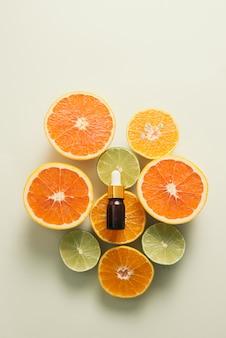 Bottiglia marrone con limone, arancia, mandarino e vitamina c su sfondo bianco