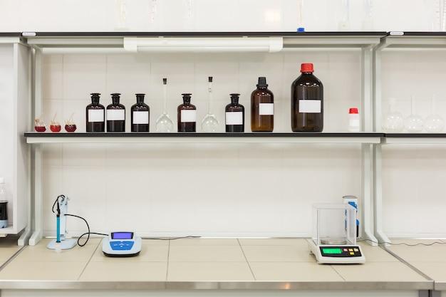 Bottiglie marroni su uno scaffale in laboratorio.