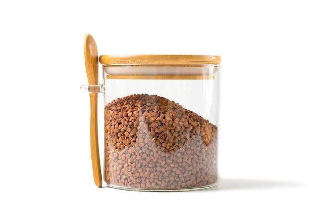 Chicchi di grano saraceno marrone in vaso di vetro con cucchiaio e coperchio in legno