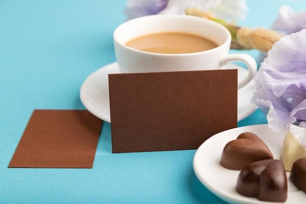 Biglietto da visita marrone con tazza di cioffee, cioccolatini e fiori di iris su sfondo blu.