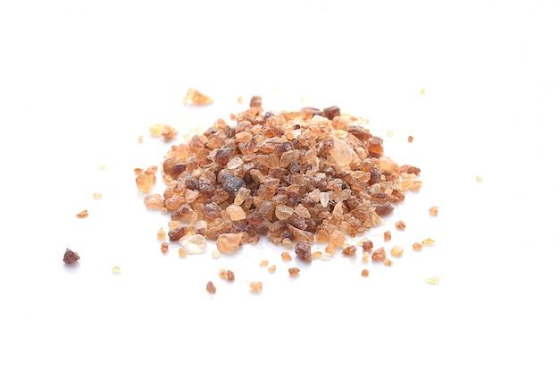 Zucchero di cristalli della caramella di brown, zucchero di roccia isolato su bianco.