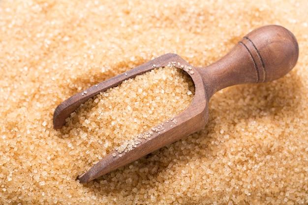 Zucchero di canna marrone con paletta di legno come sfondo