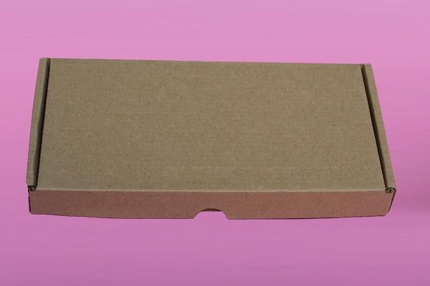 Scatola di cartone marrone per mockup su sfondo rosa. spazio per il testo