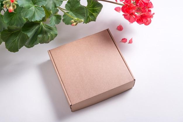 Scatola piatta di cartone marrone su sfondo bianco decorato con fiori freschi