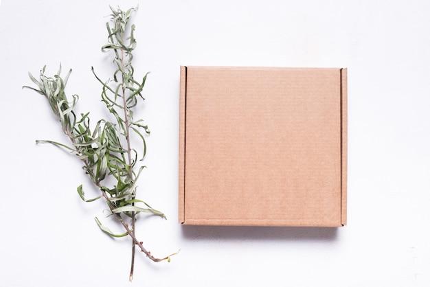 Scatola postale in cartone marrone decorata con foglie secche