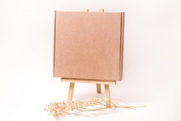Scatola di cartone marrone decorata con erba secca