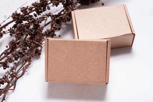 Scatola di cartone marrone decorata con rami secchi mock up
