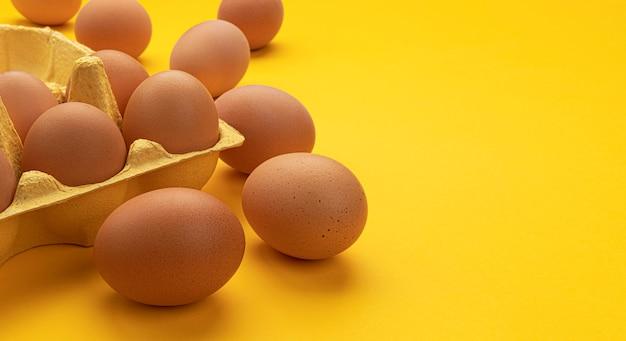 Uova di gallina marrone in scatola di cartone su spazio giallo