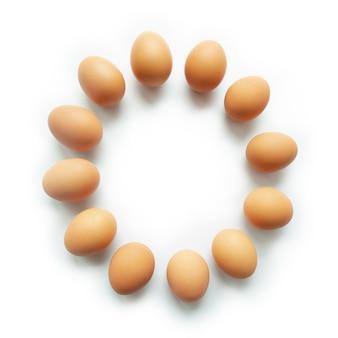 Uova di gallina marrone in cerchio tagliente su sfondo bianco.