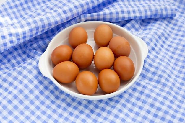 Uova di gallina marrone in piatto bianco su tessuto blu e bianco