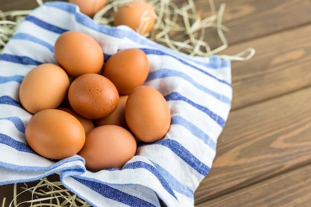 Uova di gallina marrone con un panno sul tavolo di legno.