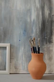Brocca di argilla marrone con gruppo di pennelli in piedi sul pavimento contro la pittura