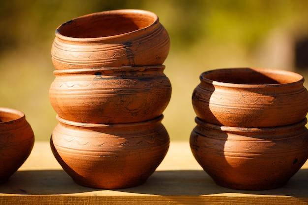 I piatti di argilla marrone stanno in fila su uno scaffale di legno