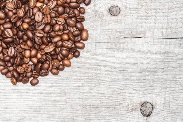 Chicchi di caffè marroni su fondo di legno di colore chiaro. copia spazio. close-up macro vista dall'alto di natura morta.