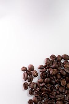 Chicchi di caffè di brown su superficie bianca