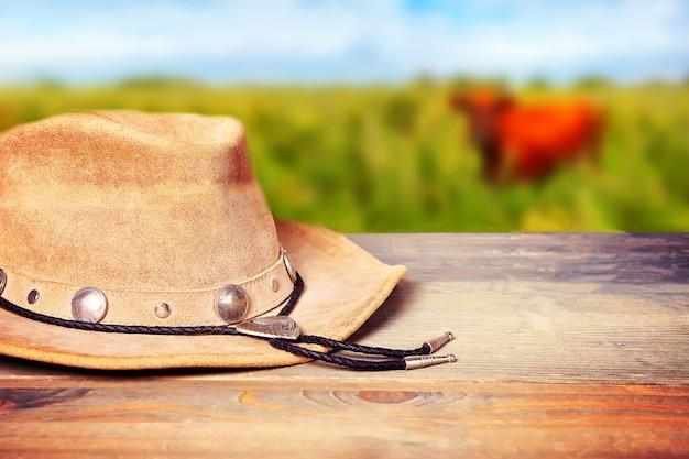 Cappello da cowboy marrone su un tavolo di legno con mucca sul prato
