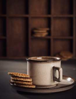 Tazza di caffè marrone e stroopwafel tradizionali olandesi. superficie alimentare con copia spazio