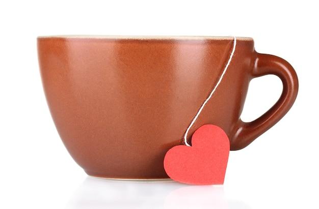Tazza marrone e bustina di tè con etichetta rossa a forma di cuore su bianco