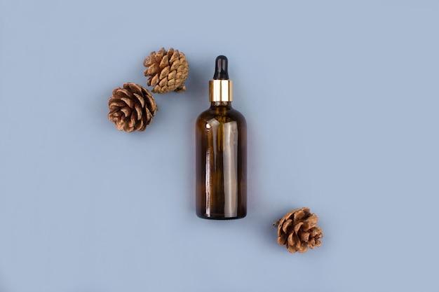 Bottiglia di vetro contagocce marrone, coni di abete distesi sul blu