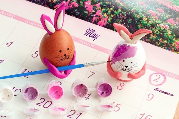 Un uovo marrone a forma di coniglietto dipinge un uovo bianco con vernice viola calendario aperto con la data di pasqua contrassegnata nel calendario di maggio