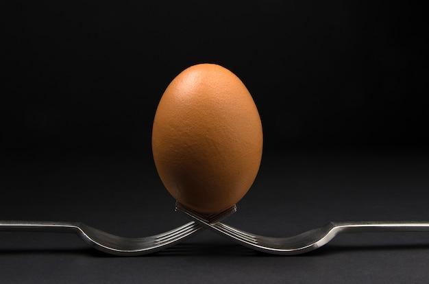 Uovo marrone trattenuto da due forchette isolate su sfondo nero