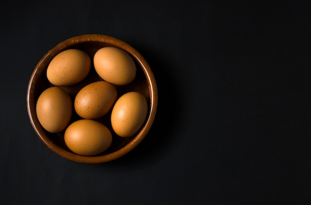 Uova marroni in una ciotola marrone isolata su sfondo nero