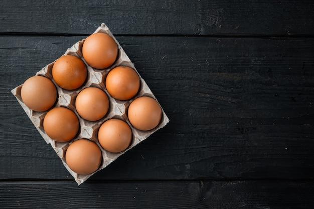 Uova di brown nel vassoio della scatola di cartone impostato, sul fondo della tavola in legno nero, vista dall'alto laici piatta, con spazio per il testo copyspace