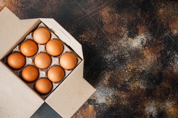 Brown uova in scatola di cartone vassoio impostato, sul vecchio scuro sfondo rustico, vista dall'alto laici piatta, con spazio per il testo copyspace