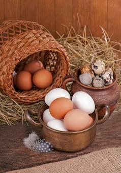 Uova di brown nel cestino di legno. uovo rotto con tuorlo in sottofondo.