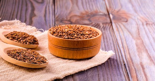 Semi di lino marroni o semi di lino in una piccola ciotola sul saccheggio e due falsi di legno su un tavolo di legno marrone