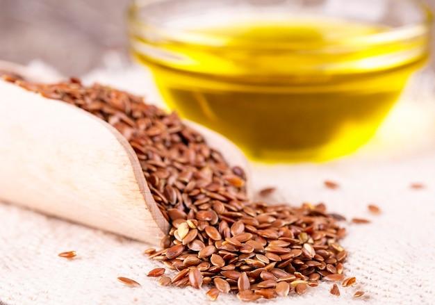 Semi di lino marroni e olio di semi di lino su una superficie di legno