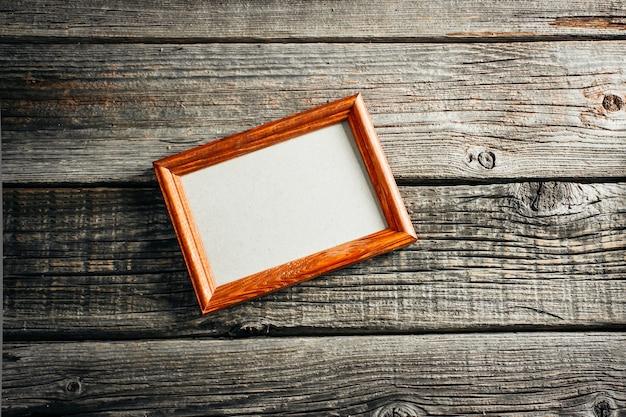 Cornice marrone su tavola di legno, vuota per foto, retrò