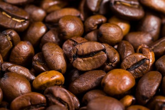 Brown chicchi di caffè appena tostati su un tavolo di legno, primo piano di semi per fare una bevanda con caffeina