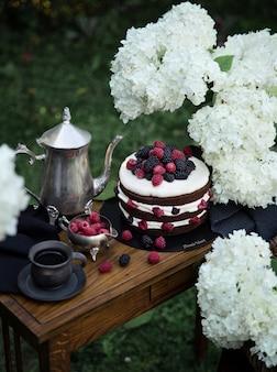 Torta di frutta marrone sul tavolo stretto di legno in giardino. teiera d'argento e due tazze di tè nere completano la composizione.