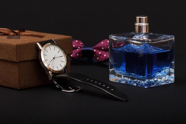 Confezione regalo marrone, orologio con cinturino in pelle nera, papillon e profumi da uomo su sfondo nero. accessori per uomo.