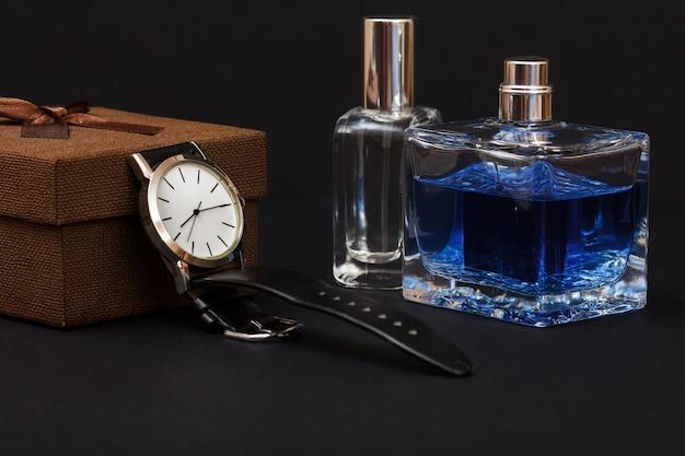 Confezione regalo marrone, orologio con cinturino in pelle nera e profumi da uomo su sfondo nero. accessori per uomo.