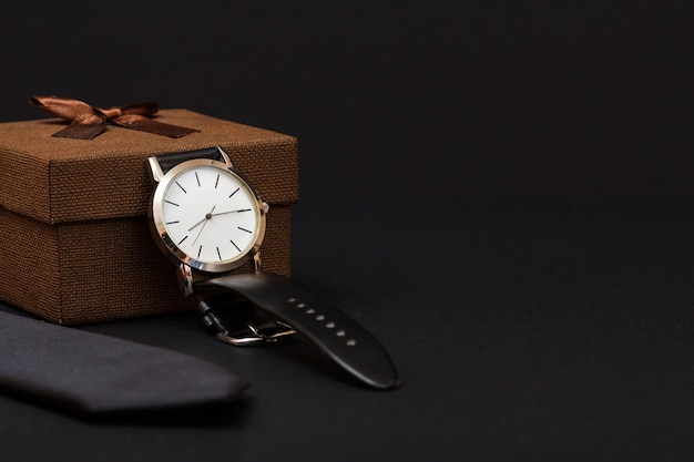 Confezione regalo marrone, orologio con cinturino in pelle nera e cravatta su sfondo nero. accessori per uomo.