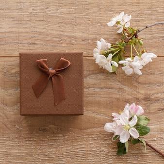Confezione regalo marrone con rami di ciliegio in fiore e meli sulla superficie in legno