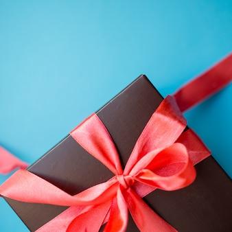 Contenitore di regalo marrone con nastro rosso su sfondo blu. vista dall'alto con lo spazio della copia.
