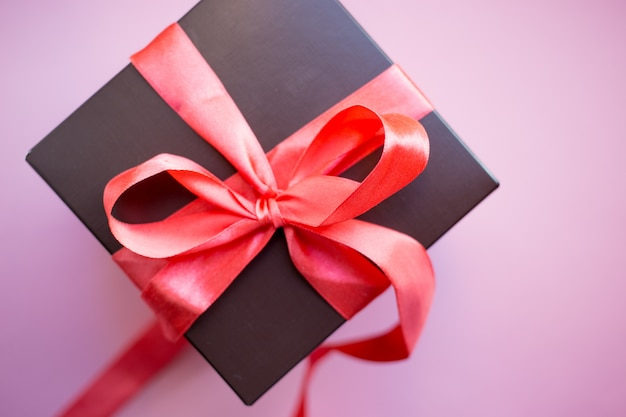 Contenitore di regalo marrone con nastro rosso su sfondo rosa. vista dall'alto con lo spazio della copia.