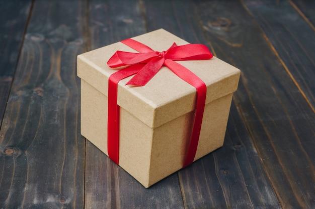 Scatola regalo marrone sul fondo della tavola in legno con lo spazio della copia.