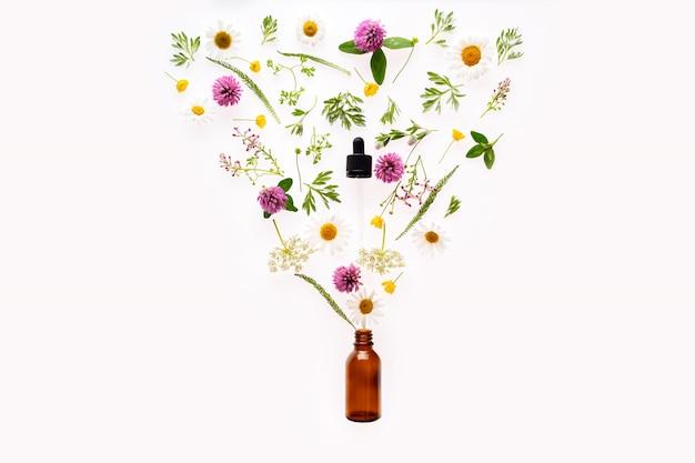 Bottiglia di vetro marrone e fiori selvatici ed erbe si riversano dal contagocce.