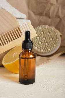 Bottiglia di vetro marrone con contagocce per siero o olio cosmetico su sfondo chiaro, concetto di cura del corpo ecologico, limone e spazzola per massaggi su sfondo