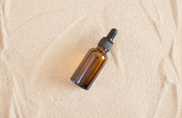 Bottiglie di vetro marrone con dosatore contagocce su fondo sabbia, flaconi per olio cosmetico o siero senza logo ed etichetta, prodotto cosmetico vuoto e mock up