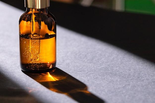 Bottiglie di vetro marrone con siero per la cura della pelle oleosa si chiudono sul tavolo bianco